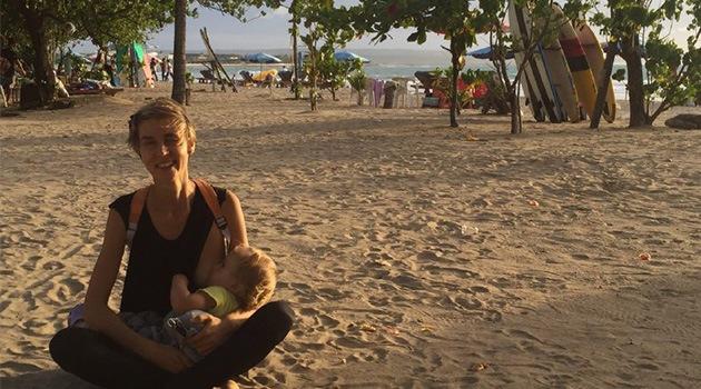 Девушка на пляже кормит грудью ребенка