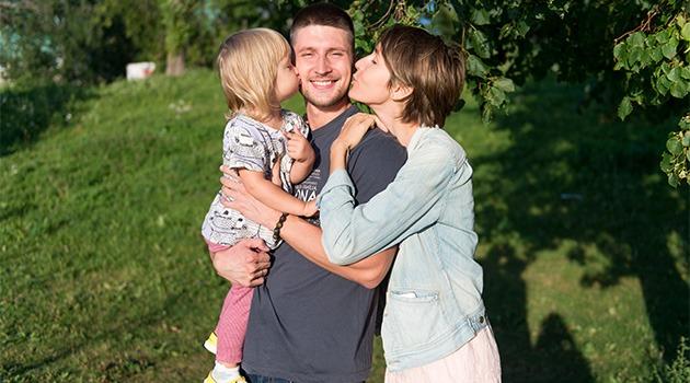 жена и дочка целуют папу