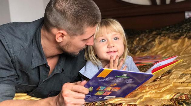 ребенок слушает как папа читает поучительную сказку